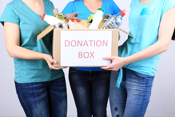 Three Ladies Holding Donation Box