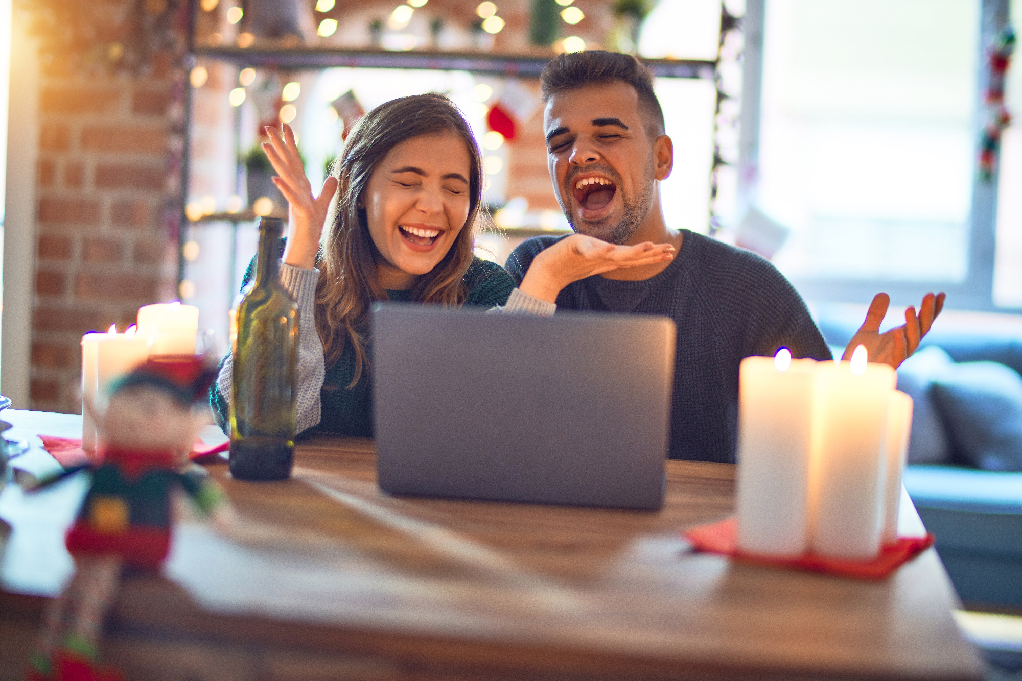 Young Beautiful Couple Sitting Using Laptop Around Christmas Decoration At Home Celebrating Mad And Crazy For Success With Arms Raised And Closed Eyes Screaming Excited. Winner Concept